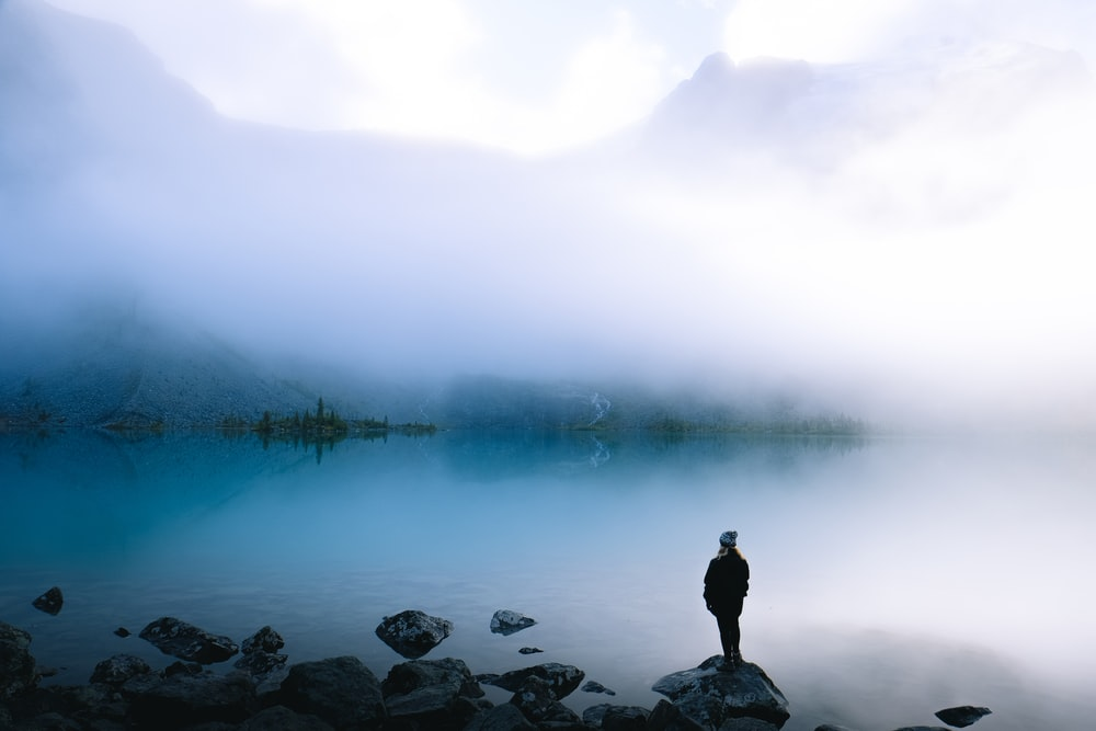 person standing on rock overlooking body of water