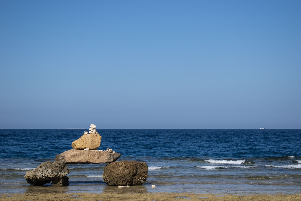 brown rocks near ocean