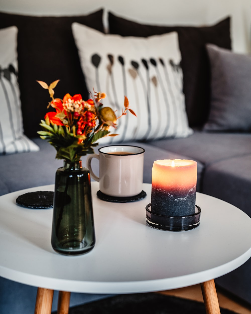 orange flower inside glass vase , lighted candle and white mug on round table