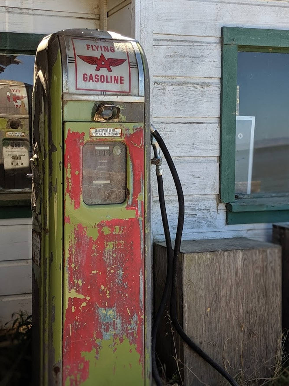 Flying Gasoline has pump by wooden housde