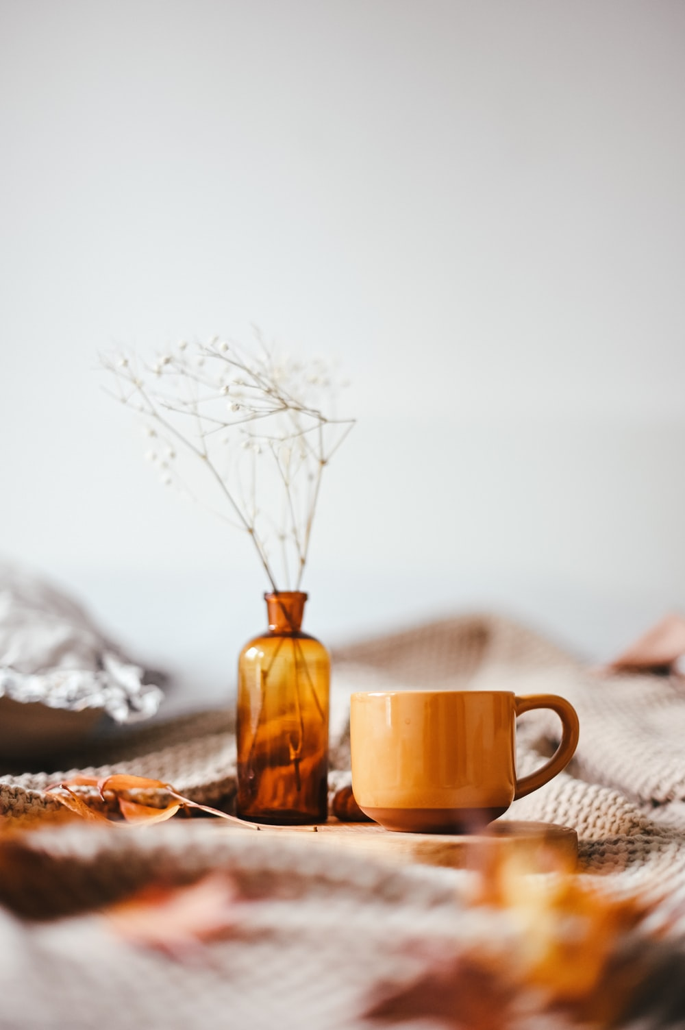brown mug beside amber vase