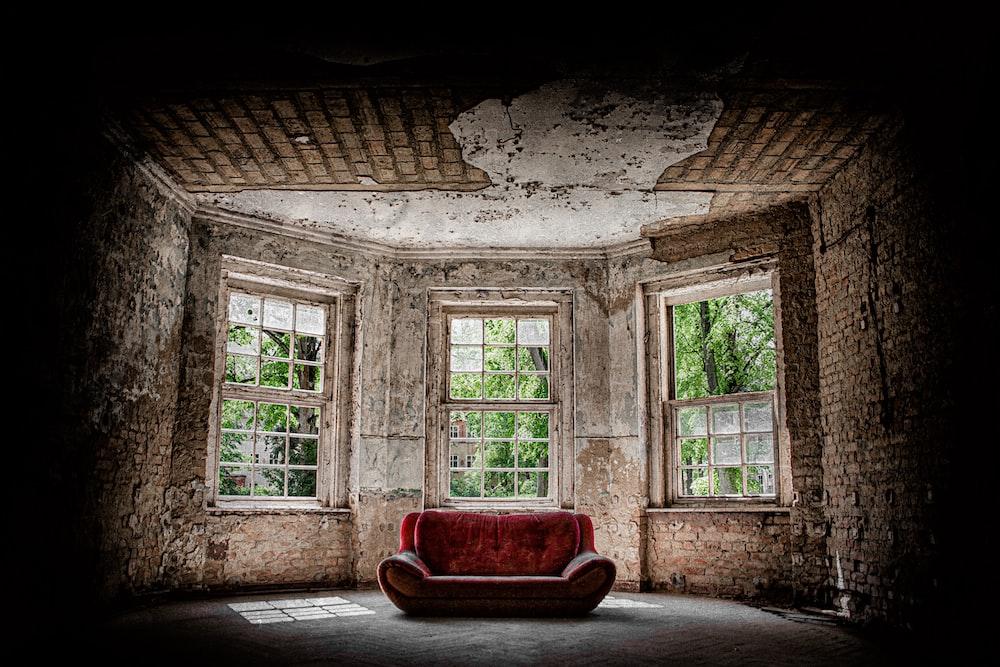 red fabric sofa near the window