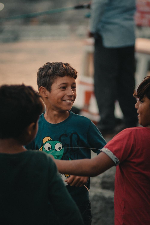 boy wearing green crew-neck shirt