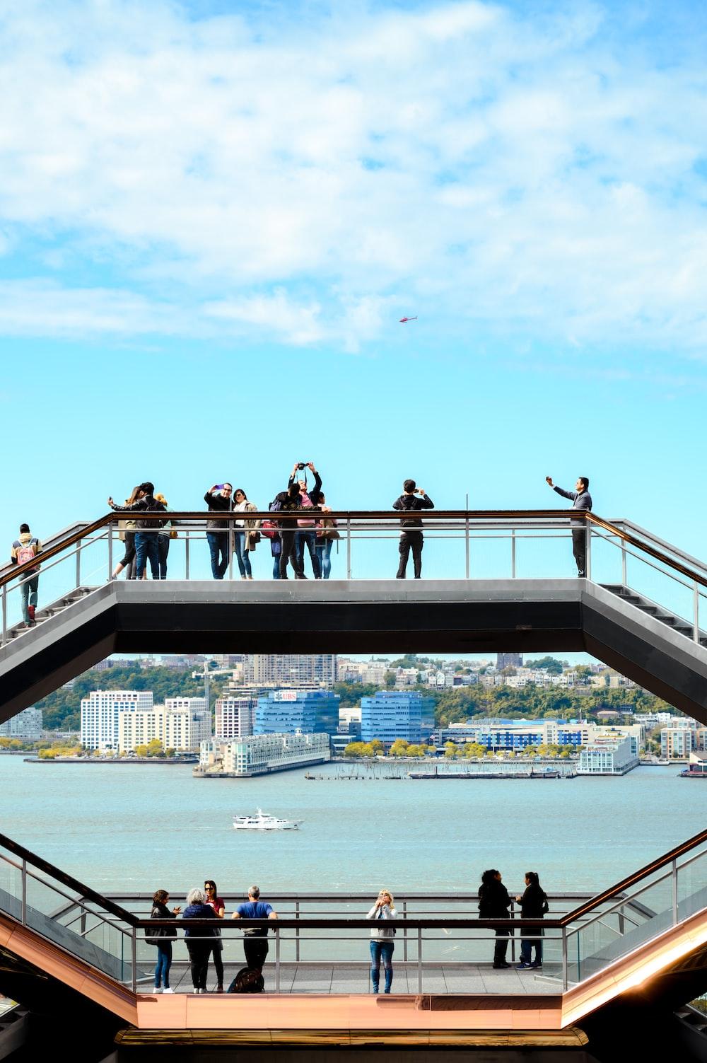 people standing on concrete bridge during daytime