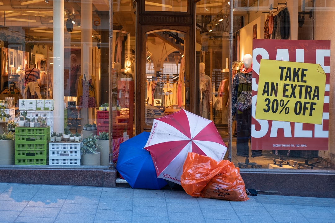 A homeless man takes shelter under opened umbrellas in the front door of a retail shop, while the shop next to him offers significant sales discounts. A juxtaposition - excess and having nothing. The lighting in the shot (the warm hues of the inside of the shop) compound the feeling of coldness on the outside.