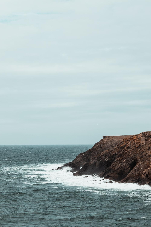 ocean wave splashing on rock during daytime