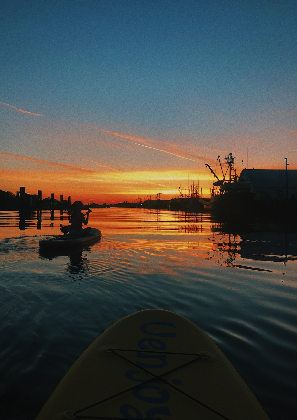 woman sits on paddleboard during sunset