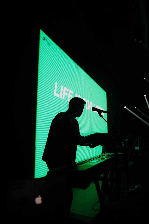 silhouette of man standing beside electric keyboard