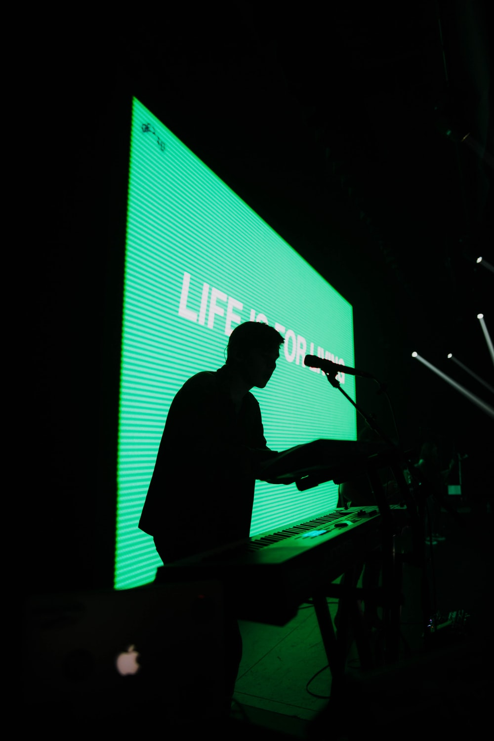 silhouette of man standing beside electric keyboard