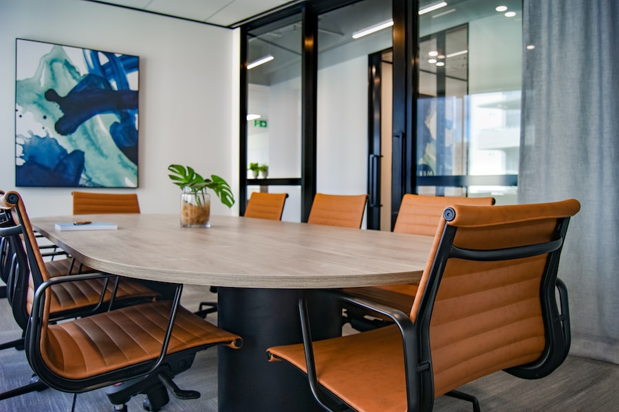 light brown 9-piece office chairs around a large circular wooden table in a glass walled office room with a blue abstract painting on the wall and monstera leaves in a vase on the table.