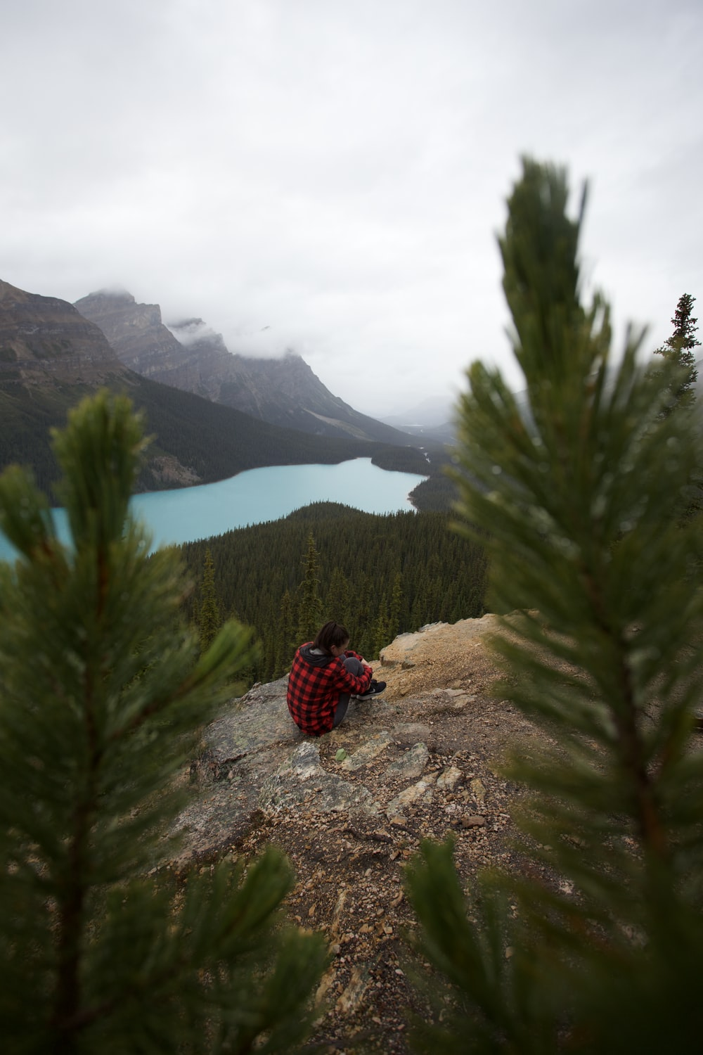 person sitting on cliff viewing mountain and lake under white and gray sky during daytime