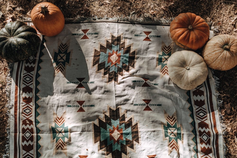 five white and orange pumpkins on white and multicolored tribal mat