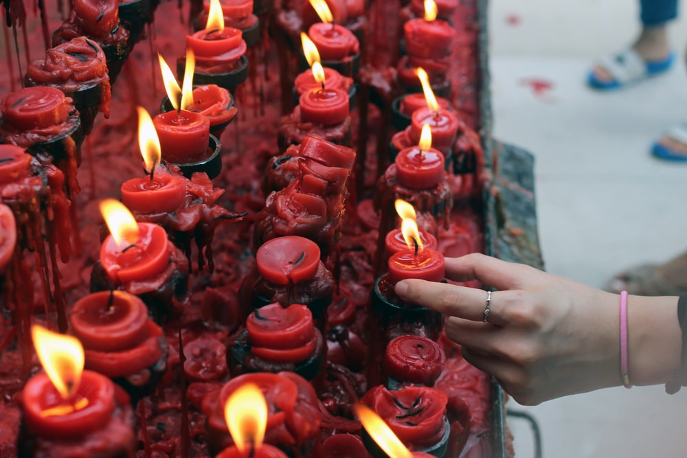 person holding red candle