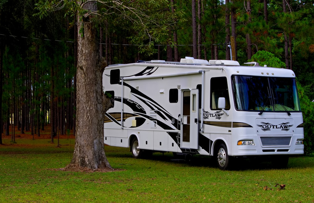 Outlaw RV parked on grass near trees