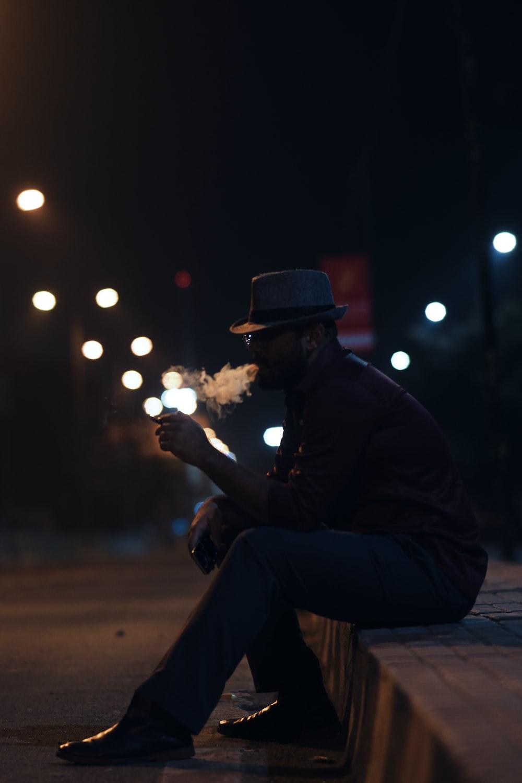 man sitting on grey concrete surface