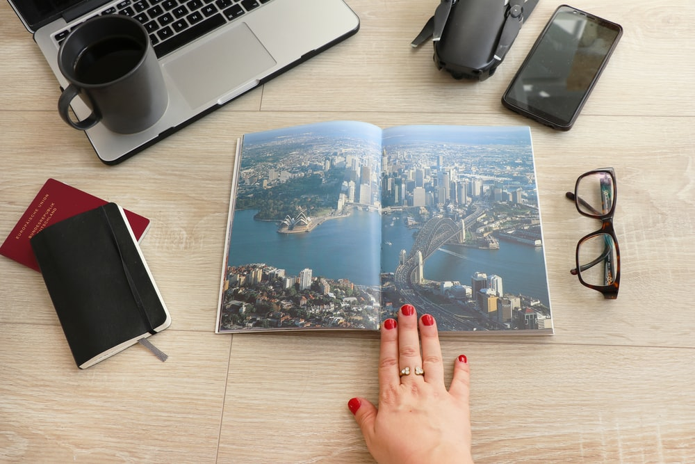 city and sea graphic opened book beside eyeglasses and laptop