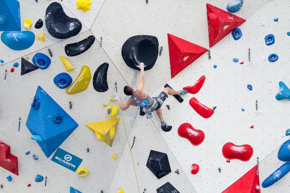 man wearing gray tank top climbing on wall