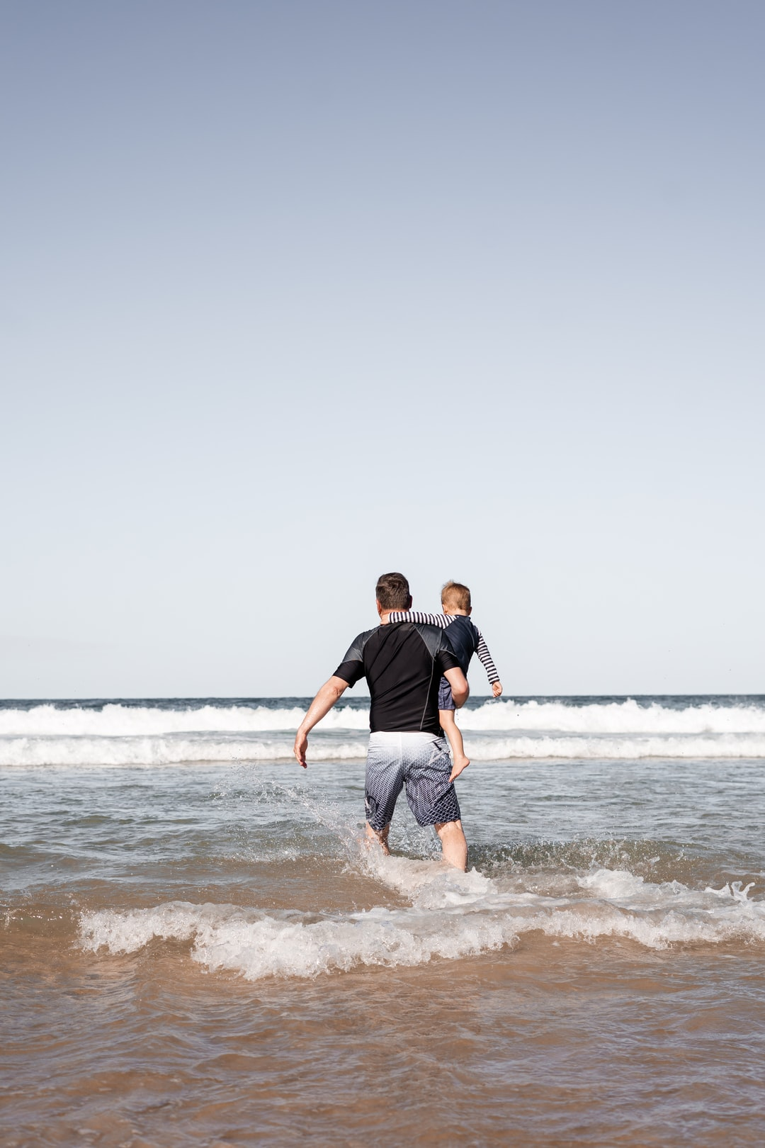 Grandfather and Grandsong running on the beach