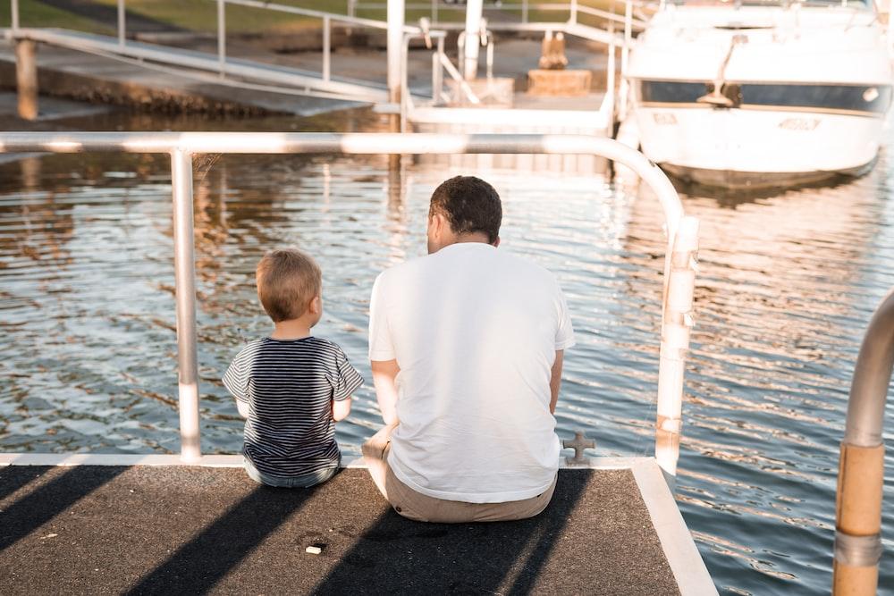 man and boy sitting on dock