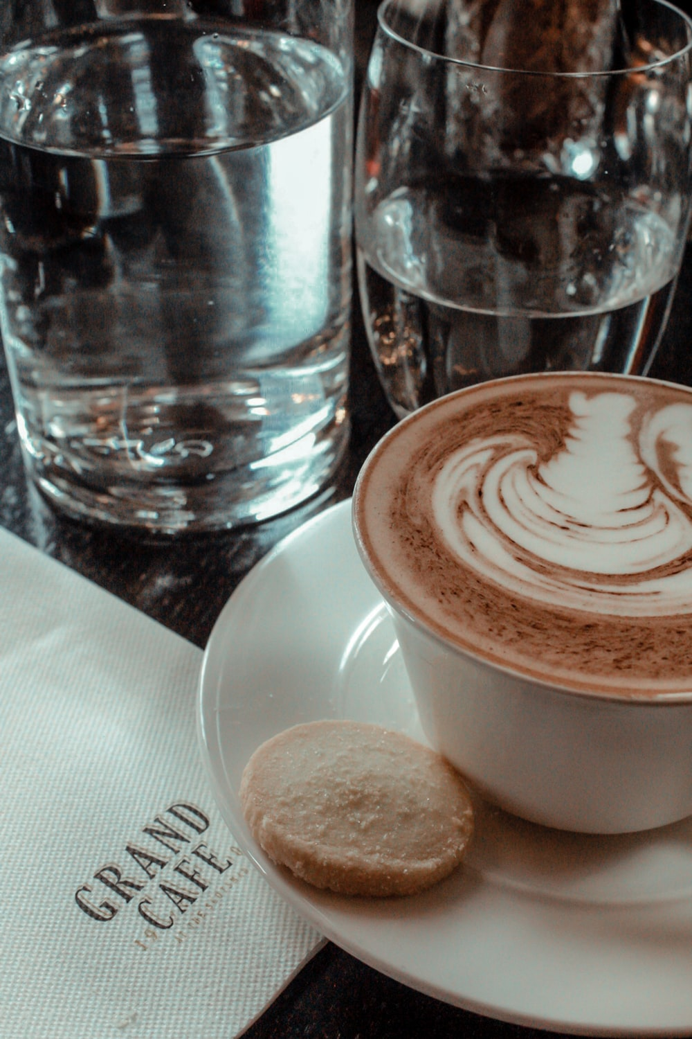 cup of latte and biscuit on saucer