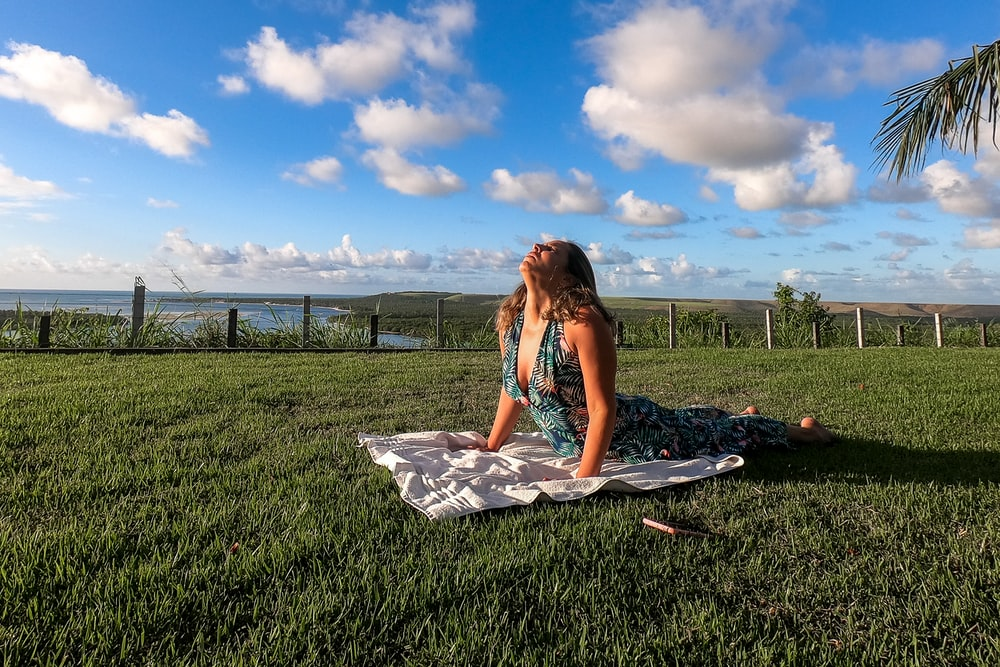 woman in green sleeveless dress doing yoga outdoor during daytime