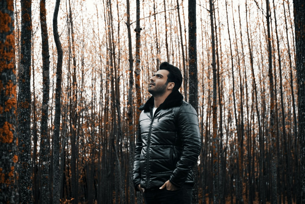 man in leather jacket in forest