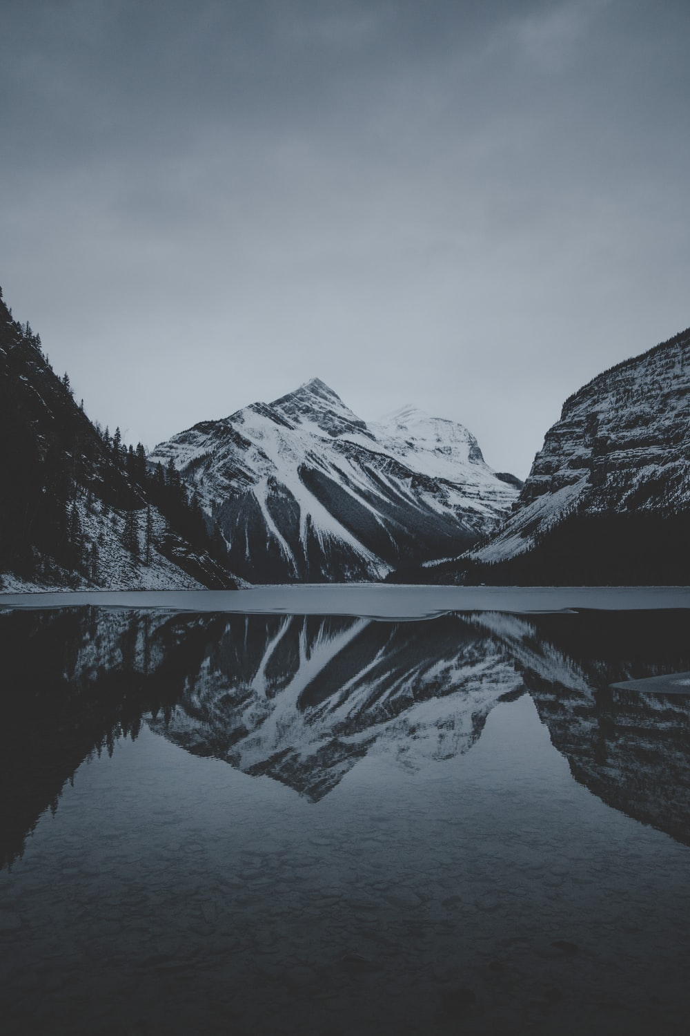 snow mountains and lake undr gray sky