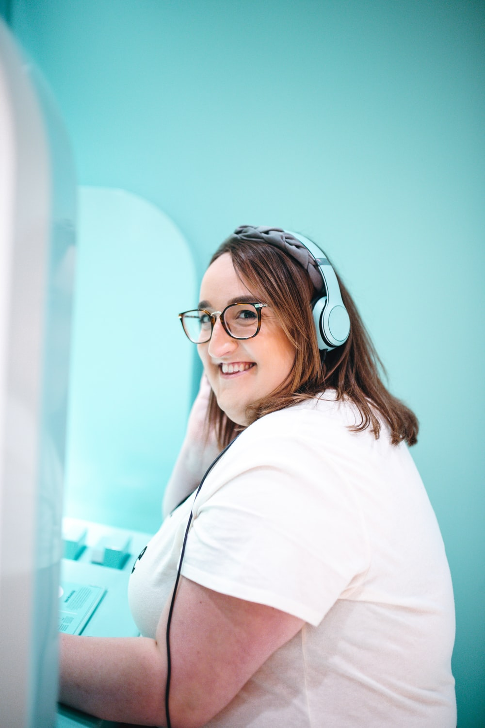 woman in white T-shirt using blue headphones