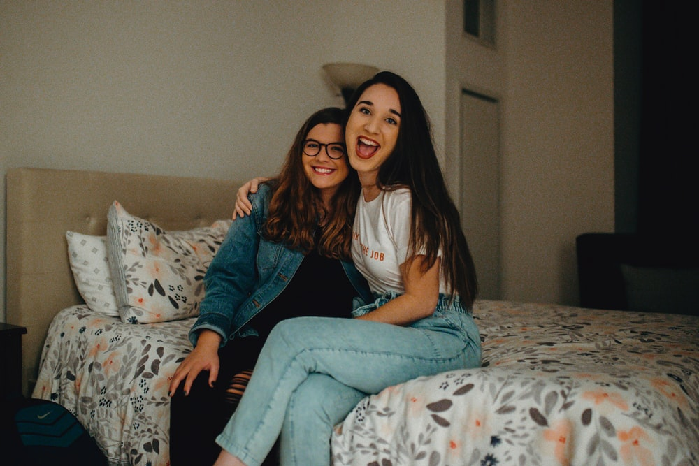 two women smiling while sitting on bed