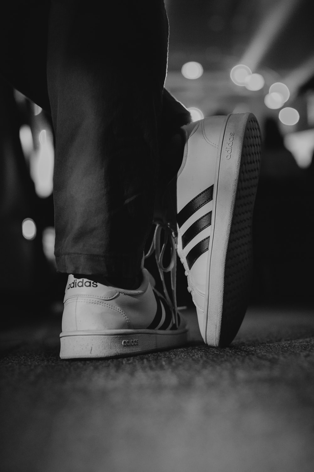 person wearing adidas low-top sneakers