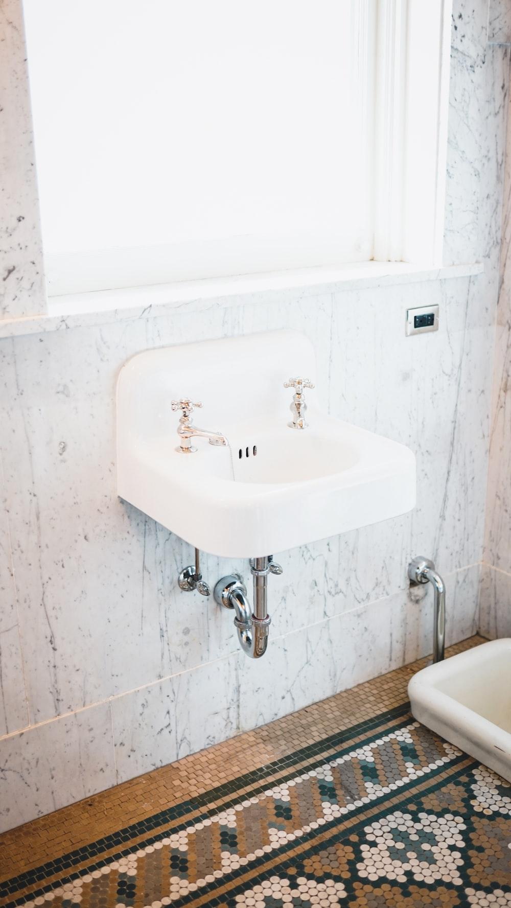 two faucet on sink near window