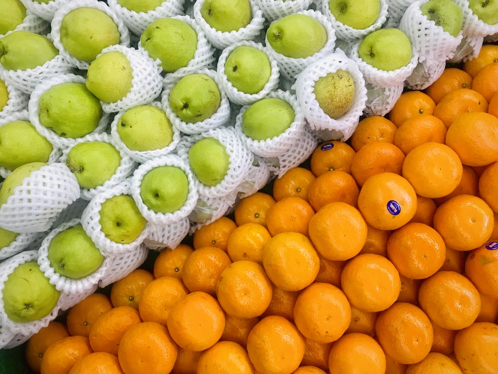 pile of green apples and orange fruits