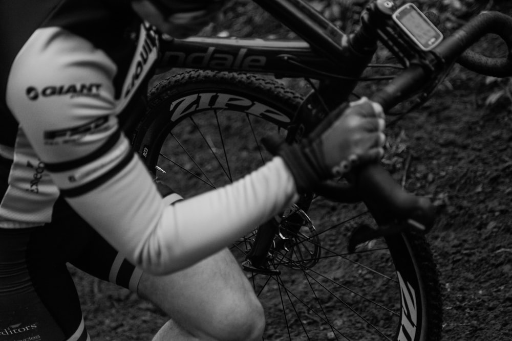 grayscale photography of man holding bike