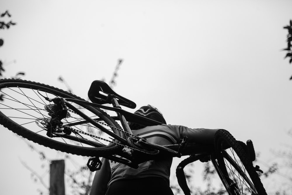 greyscale photography of man carrying bike