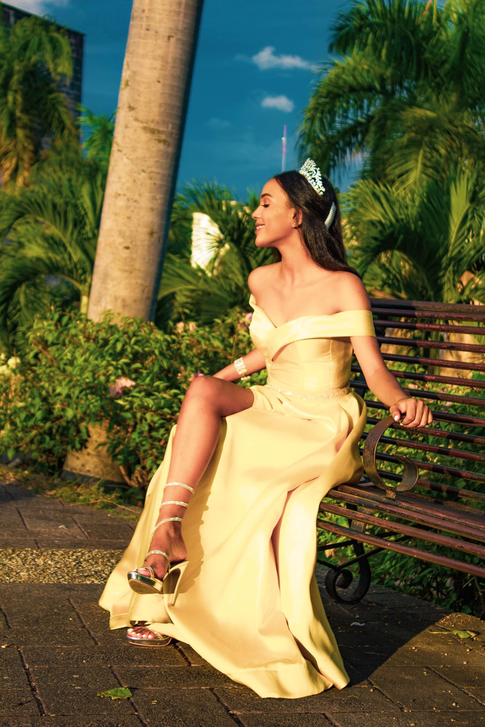 woman wearing yellow off-shoulder silt dress with silver-colored tiara sitting on brown bench