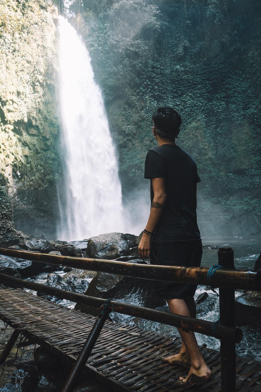 man wearing black crew-neck shirt walking on brown bridge