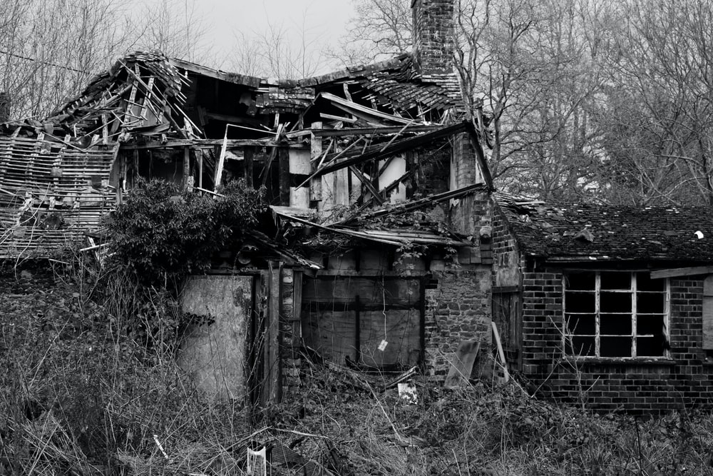 grayscale photo of wrecked house