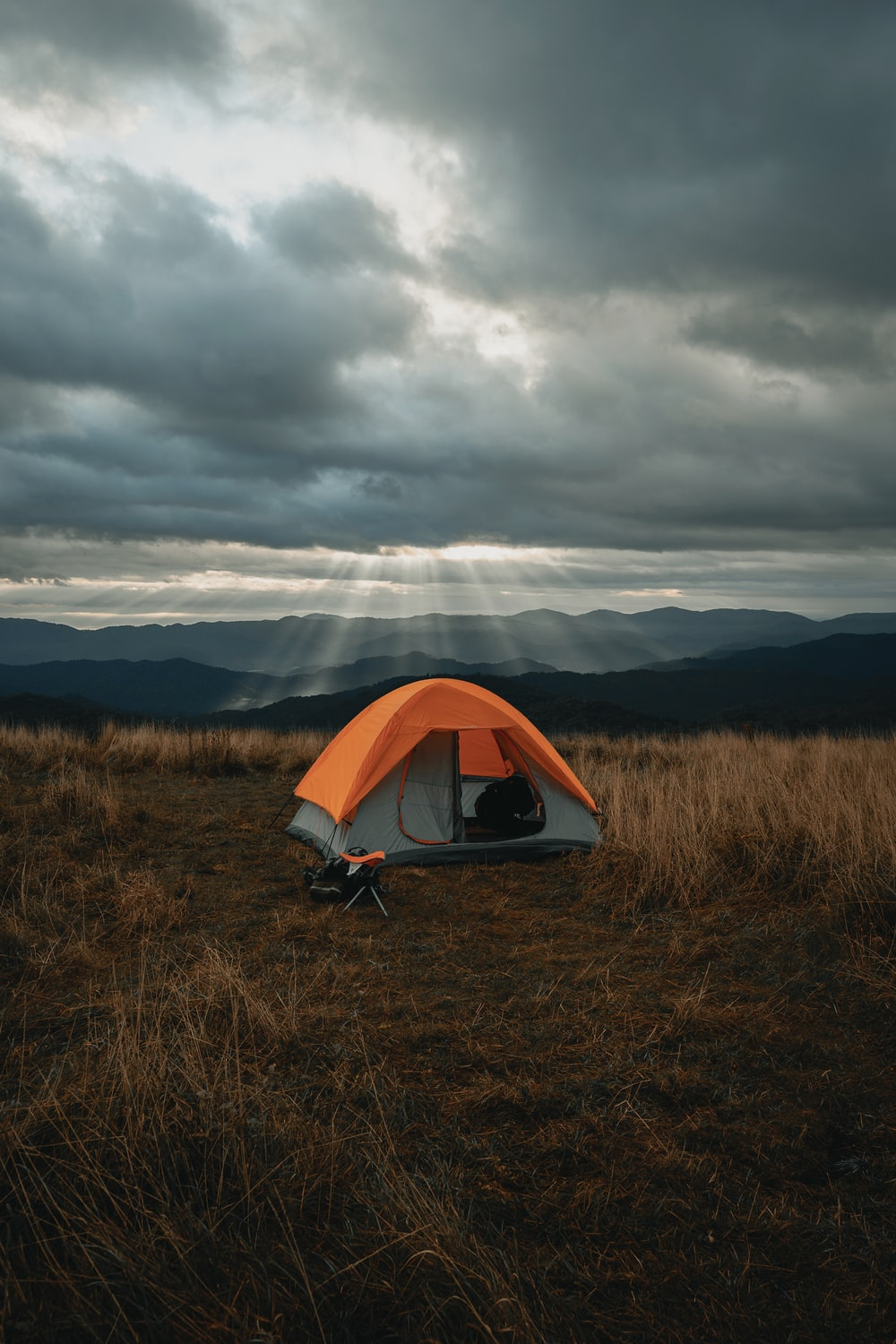 set-up gray and orange tent on brown field under cloudy sky