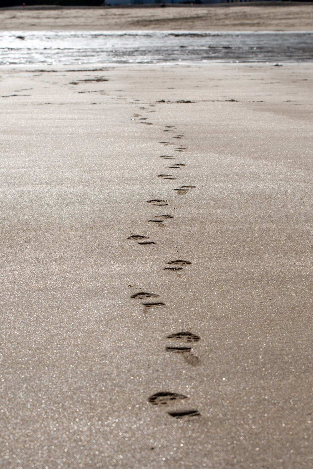 sand with footprints during day