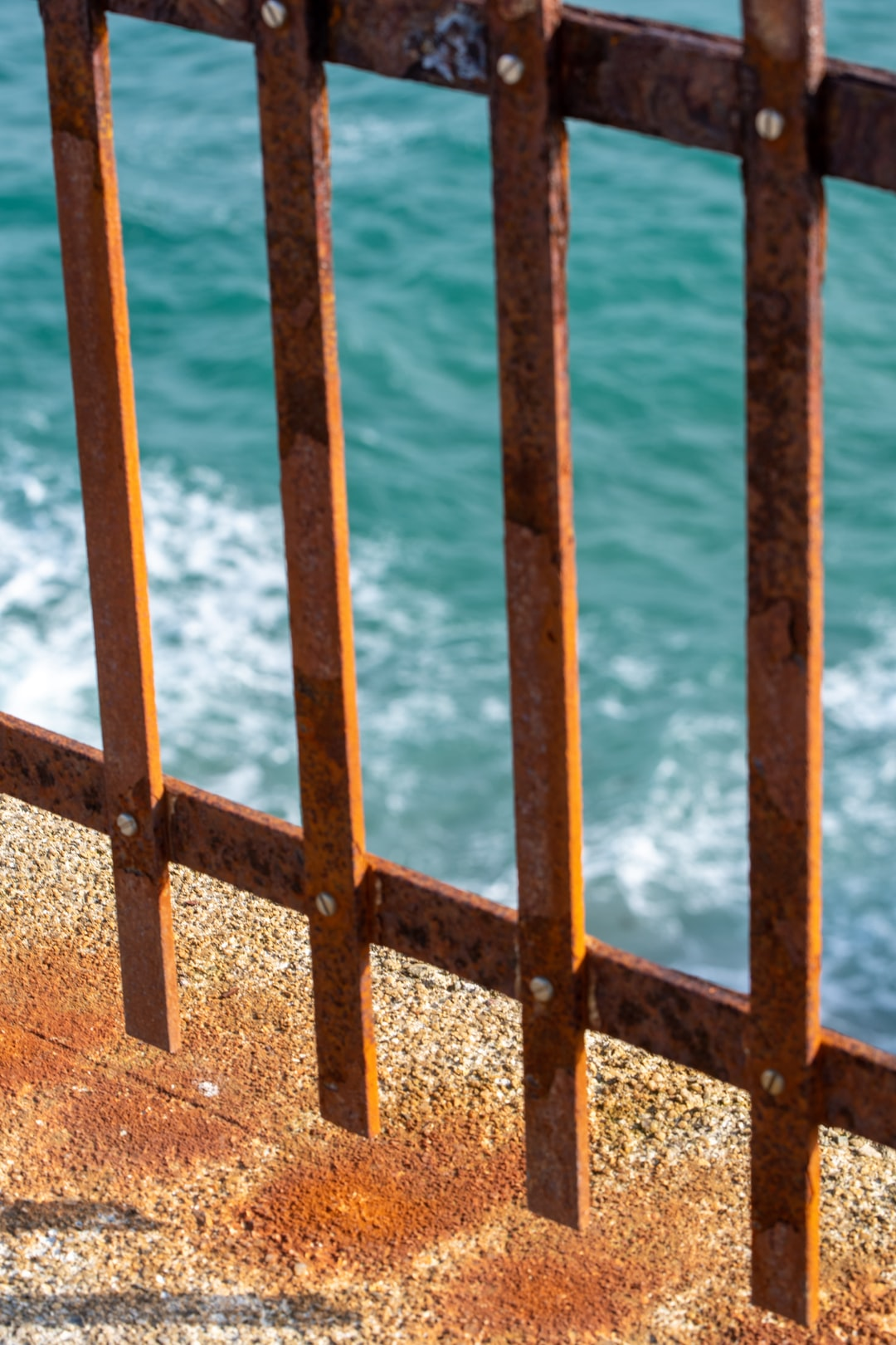 A rusty gate in front of the blue ocean in Cornwall, UK.