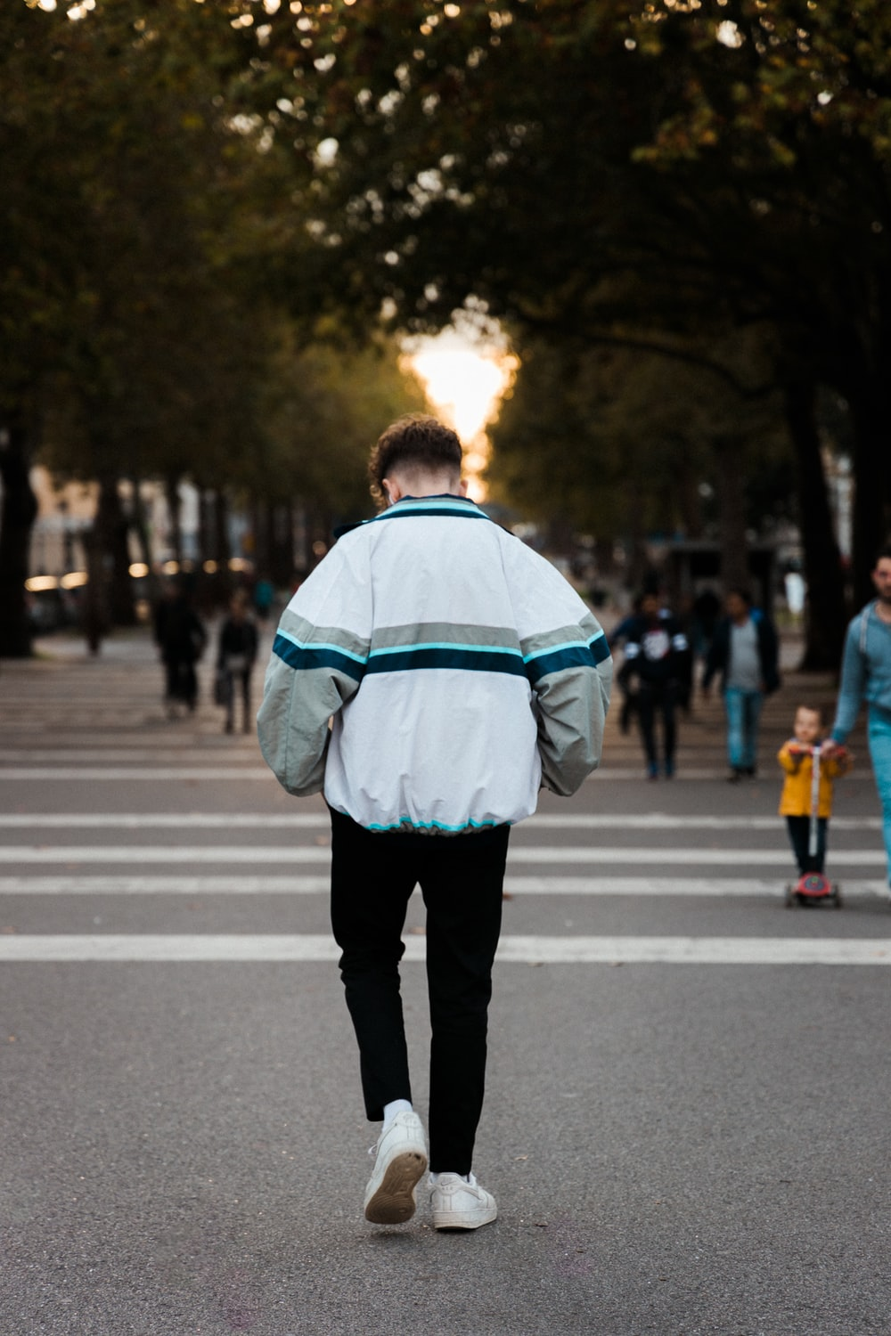 man wearing white and blue jacket and black jeans walking on street