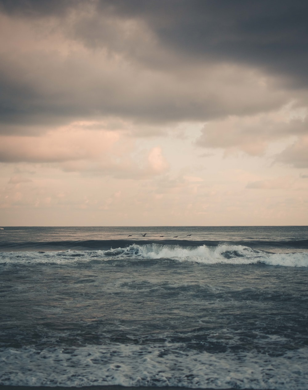 sea waves under cloudy sky during daytime