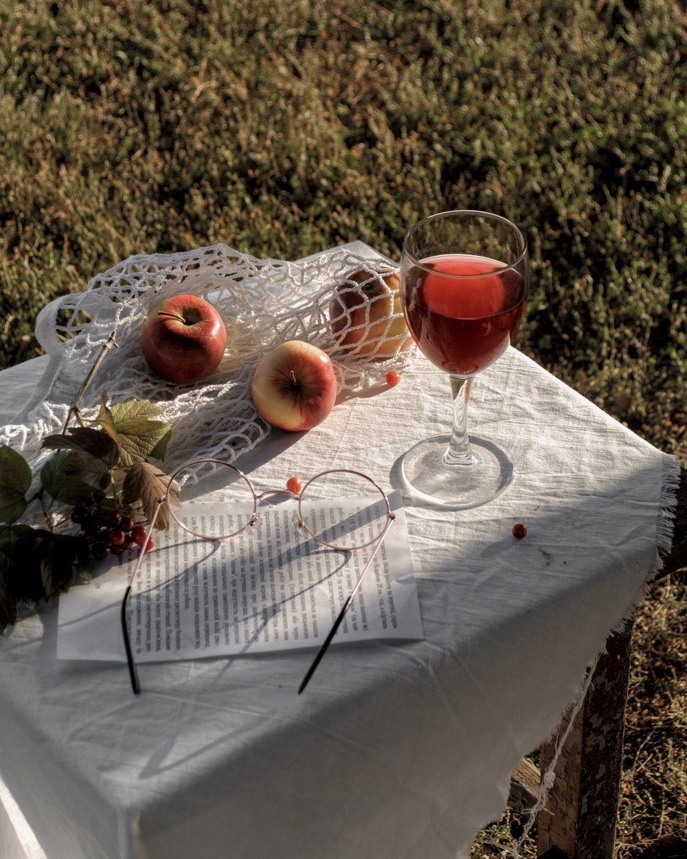 glass of red wine near three apple fruits on table