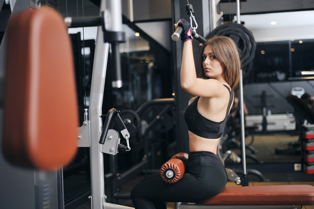 woman in black sports bra exercising using lat pull down machine