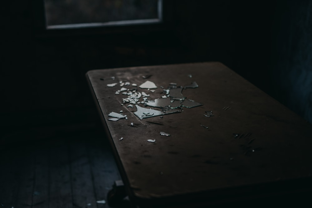 close-up photo of brown wooden table inside dark room
