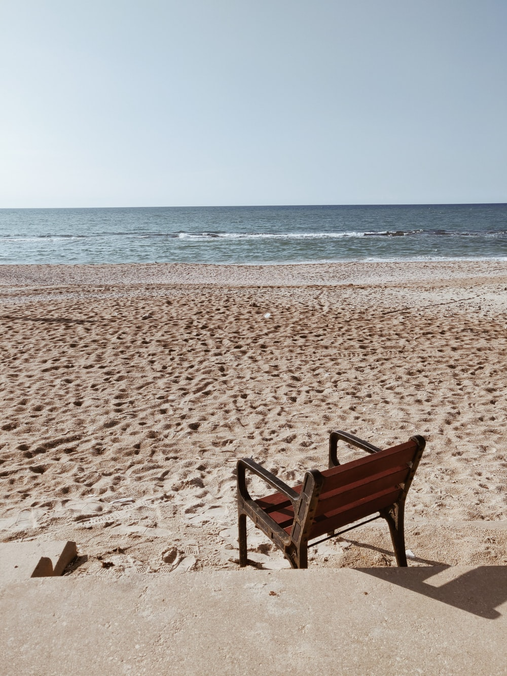 black wooden bench and two brown wooden chairs
