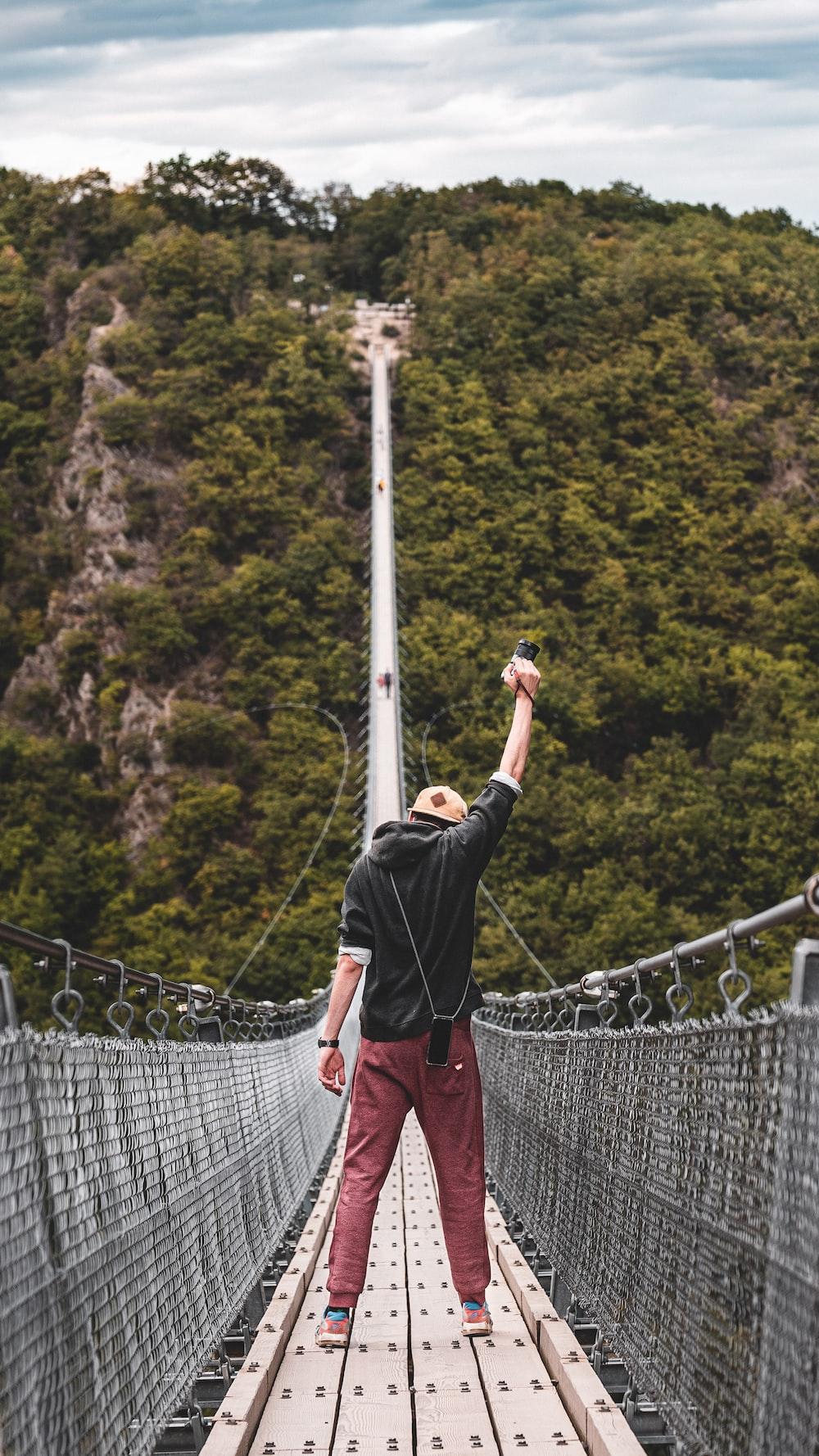 man standing on bridge during daytime