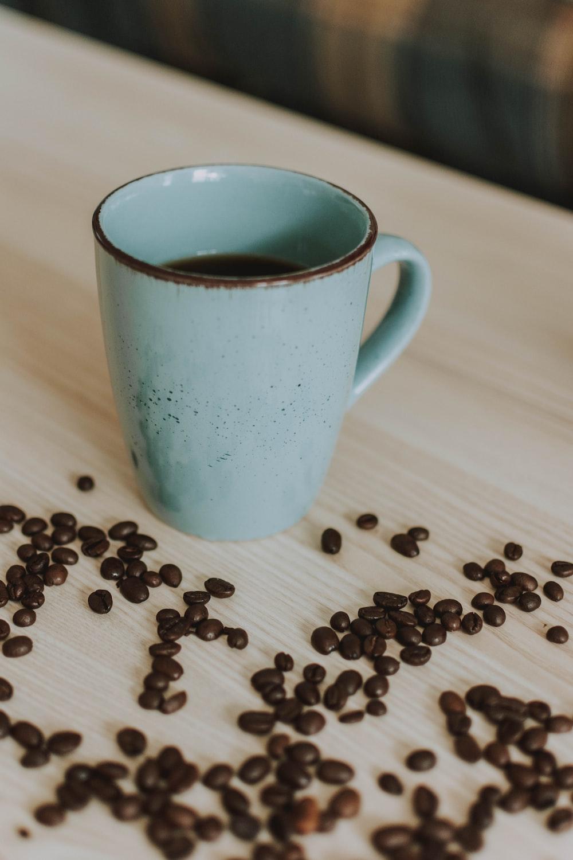 teal ceramic mug beside coffee beans on table