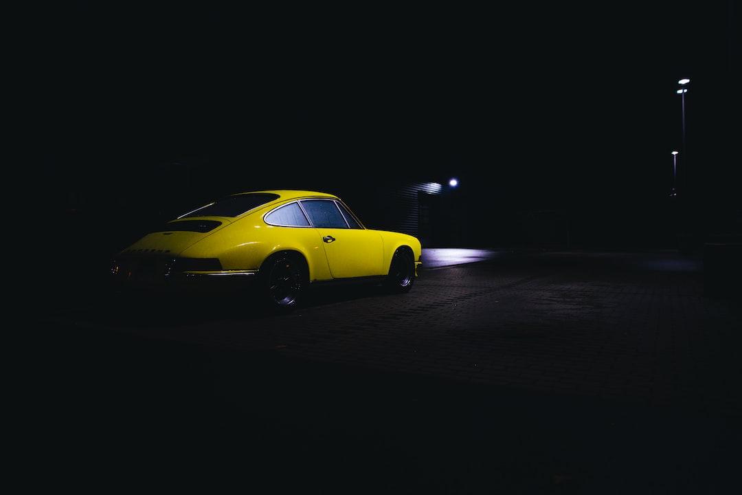 Yellow iconic vintage Porsche 911 sportscar at night.