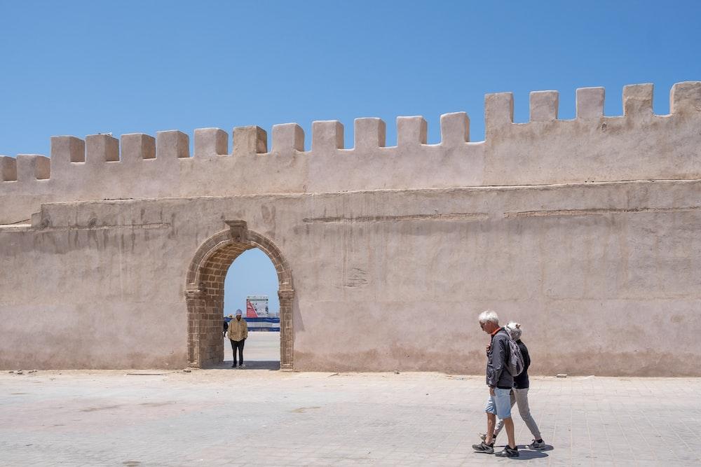 two people walking near wall